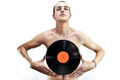 Dj with vinyl. Nude dj with tattoos on arms holding a vinyl record in front of him Royalty Free Stock Image