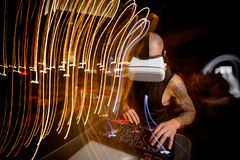DJ in virtual reality glasses yurns the records in night club Stock Photos