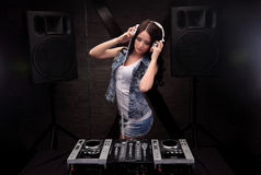 Dj with white headphones playing music on mixer with light beam effects. Loudspeakers on background. Young woman dj in headphones playing music on mixer on Royalty Free Stock Photos