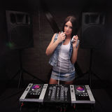 Dj with white headphones touching her lip with finger. Loudspeakers on background mixer on table Stock Photography