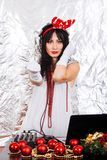DJ woman New Year Santa costume headphones silver background party girl red horns christmas decorations brunette white dress royalty free stock photo
