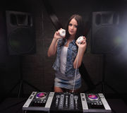 Dj woman showing white headphones playing music on mixer with light beam effects. Loudspeakers on background. Young woman dj in headphones playing music on Stock Images