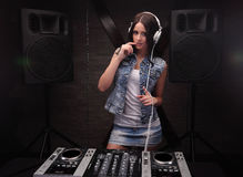 Dj woman with white headphones on her head. Loudspeakers on background. Young woman dj in headphones playing music on mixer on table Stock Image