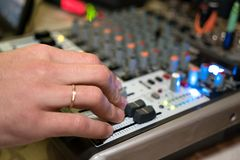 DJ working on a audiomixer at a nightclub royalty free stock photography