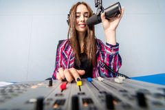 Dj working on the radio. Female dj working in front of a microphone on the radio Stock Photos
