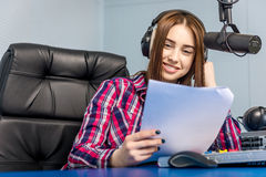 Dj working on the radio. Female dj working in front of a microphone on the radio Royalty Free Stock Photos