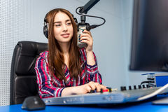 Dj working on the radio. Female dj working in front of a microphone on the radio Stock Image