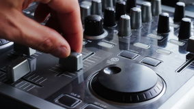 DJ Working with Sound mixing console. DJ working with an analog audio mixer. Fingers hand man to raise and lower the fader, Spin a Jog Wheel, turn the handle and stock footage