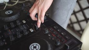 DJ's hands. A mixing remote to collect signals and play.