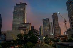 DJAKARTA, INDONESIË - 3 MAART, 2017: Modern deel van stadshorizon zoals die van afstand, mooie zonsonderganghemel met purple word Royalty-vrije Stock Fotografie