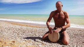 Djembe Drum Player beat rythm on the lonely beach Royalty Free Stock Photo
