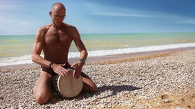 Djembe traditional Drum Player beat rythm on the lonely beach stock footage