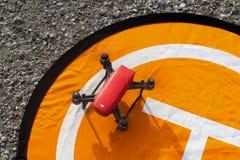 DJI προκαλεί την προσγείωση σε ένα πορτοκαλί προσγειωμένος μαξιλάρι στο πεζοδρόμιο αμμοχάλικου με τους στροφείς γυρίζοντας ακόμα  στοκ εικόνα με δικαίωμα ελεύθερης χρήσης