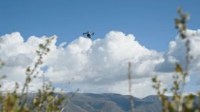 DJI Inspire-1 PRO drone rises into the air among the mountains. 50 fps stock video footage