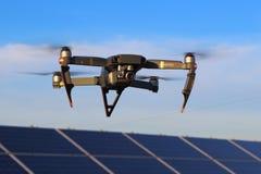 DJI Mavic Pro drone in flight above solar panels Stock Image