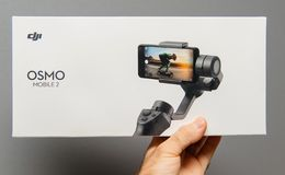 DJI Osmo Mobile 2 Smartphone Gimbal packaging. PARIS, FRANCE - NOV 22, 2018: Man hand holding against gray background new DJI Osmo Mobile 2 Smartphone Gimbal royalty free stock photo