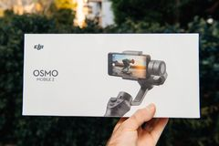 DJI Osmo Mobile 2 Smartphone Gimbal packaging. PARIS, FRANCE - NOV 22, 2018: Man hand holding in outdoor background new DJI Osmo Mobile 2 Smartphone Gimbal stock photos