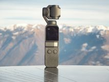 Dji Osmo pocket gimbal. Alps mountain range in the background. Electronic object royalty free stock images