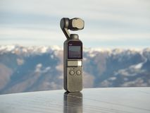 Dji Osmo pocket gimbal. Alps mountain range in the background. Electronic object royalty free stock photography