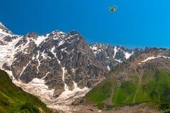 DJI Phantom 2 Vision+ standard quad-copter flying into Caucasus mountains. In Georgian Svaneti region. Beautiful large glacier Royalty Free Stock Image