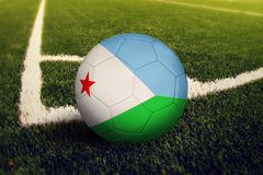 Djibouti ball on corner kick position, soccer field background. National football theme on green grass.  royalty free stock photo
