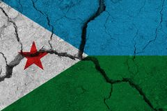 Djibouti flag on the cracked earth. National flag of Djibouti. Earthquake or drought concept stock images