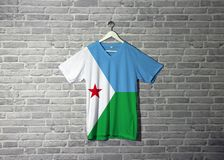 Djibouti flag on shirt and hanging on the wall with brick pattern wallpaper. A horizontal light blue and light green with a white triangle at the hoist bearing royalty free stock photography