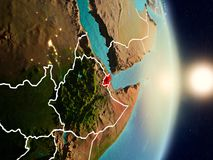 Djibouti during sunrise. Highlighted in red on planet Earth with visible country borders. 3D illustration. Elements of this image furnished by NASA Royalty Free Stock Image