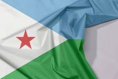Djibouti tkaniny flaga zagniecenie z biel przestrzenią i krepa obraz stock