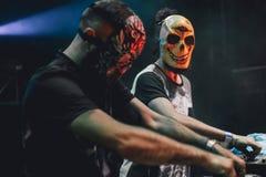 Djs με τις μεξικάνικες μάσκες που παίζουν αναμιγνύοντας τη μουσική στο φεστιβάλ κομμάτων Διασκέδαση, νεολαία, ψυχαγωγία και έννοι Στοκ Εικόνες