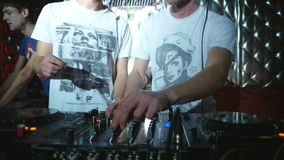 DJs control the mixing desk moving faders and knobs to the disco club in the light of flares stock video footage