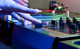 DJs hand tweaks the cross fader of a music mixer Royalty Free Stock Photos