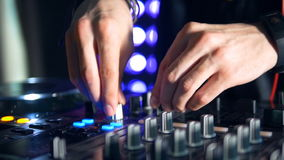 DJs hands twist a turntable and add volume. A closeup on a twisted turntable and used mixer switches stock video footage