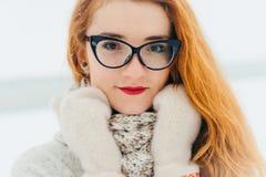 Djup sikt av de bärande exponeringsglasen för attraktiv röd head kvinna Time-utgifter i bygden under snöfallet royaltyfria foton