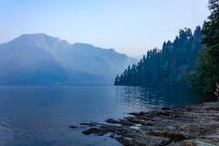 Djup skuggor och skymninghögryggad träsoffa över bergsjön arkivbild