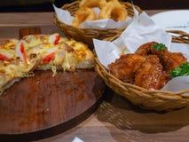Djup stekt kyckling i en korg med persilja- och skaldjurpizzatoppning med krabban, räka och skinka på ett trämagasin och lökcirkl Arkivbilder