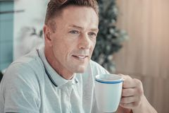 Djup stilig man som dricker te och åt sidan ser royaltyfri bild