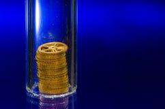 Djup syn på ett torn av klockakugghjul under den Glass lilla medicinflaskan Arkivbild