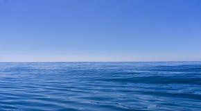 Djupblå oljig seende yttersida för abstrakt bakgrund av havet Arkivbilder