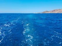 Djupblått hav och ö med liten buskesikt från baksida av a Arkivfoto