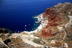 Djupblått hav och brant rött berg med en serpantineväg santorini för ö för byggnadsgreece kull royaltyfria bilder