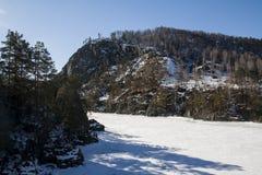 Djupfryst bergflod under is i vinter arkivfoton