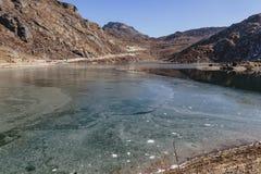 Djupfryst damm med is på den djupfrysta yttersidan med det bruna berget och klar himmel i bakgrunden i vinter i Tashi Delek Arkivfoton