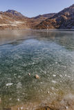 Djupfryst damm med is på den djupfrysta yttersidan med det bruna berget och klar himmel i bakgrunden i vinter i Tashi Delek Fotografering för Bildbyråer