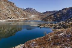 Djupfryst damm med is på den djupfrysta yttersidan med det bruna berget och klar himmel i bakgrunden i vinter i Tashi Delek Royaltyfria Bilder