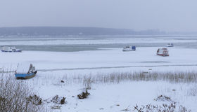 Djupfryst Donau på is med fem lilla fiskebåtar Royaltyfri Fotografi