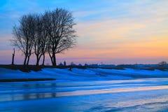 Djupfryst flod på solnedgången Arkivbild