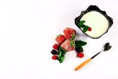Djupfryst hallon, björnbär, jordgubbar, yoghurtplatta, mintkaramellsidor, sked på en bästa sikt för vit bakgrund, slut upp, uppsä Fotografering för Bildbyråer