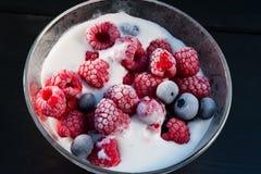 Djupfryst hallon och blåbär med glass i en glass bunke Fotografering för Bildbyråer