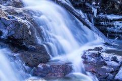 Djupfryst inloggning en vattenfall arkivfoton